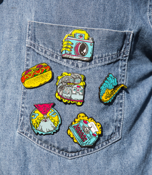 "In 2016, Unkefer designed a set of lapel pins for Admissions. The nine pins reflect Unkefer's signature, cartoony style. ""I can be a very crazy, bright, saturated cartoony, highly stylized, drippy, gooey-making artist,"" says Unkefer. The illustrations include art objects such as a typewriter, saxophone and camera, as well as Chicago homages like a deep-dish pizza and a smiling Willis Tower."