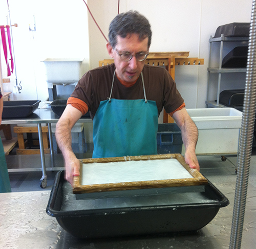 Jeff pulls out a sheet of paper, which is resting on top of a mold and topped by the wood frame (deckle).