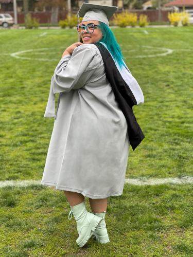 Valentine in silver cap and gown, turned away from camera, looking back.