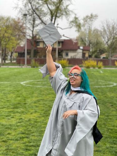 Valentine in a silver graduation gown, tossing their cap into the air.