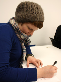 Book and Paper MFA student Kaitlin Kostus takes notes during a critique.